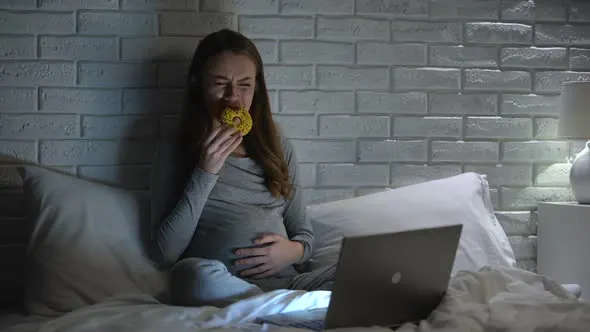 Young pregnant woman over eating