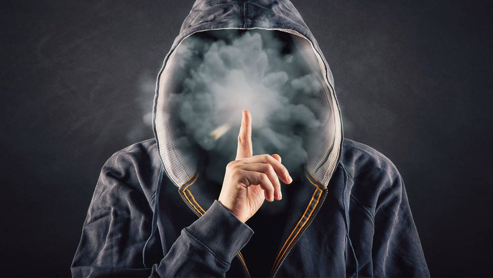 Hooded man smoking weed