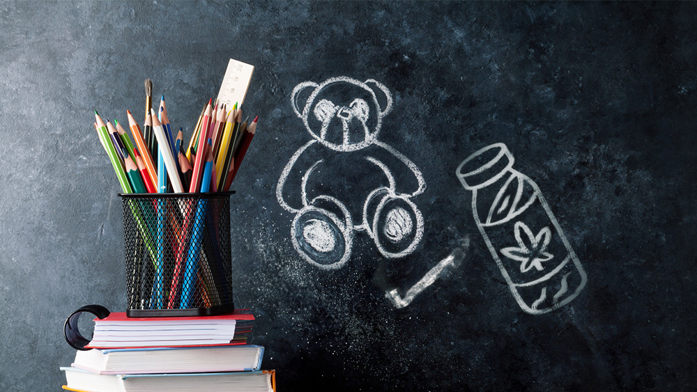 Colored panciles and drawings of a teddy bear and a bottle on a blackboard
