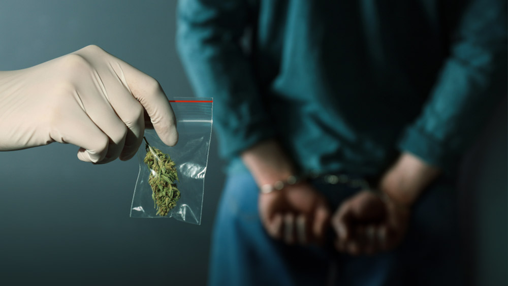 Man in a prisoner's suit and handcuffs, and another holding a bag of weed